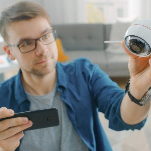 homme-avec-camera-surveillance-et-smartphone