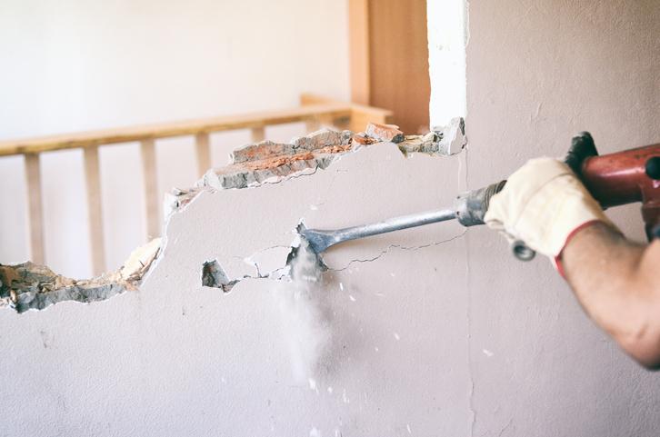 Un mur est en train d'être ouvert à l'aide d'un marteau piqueur