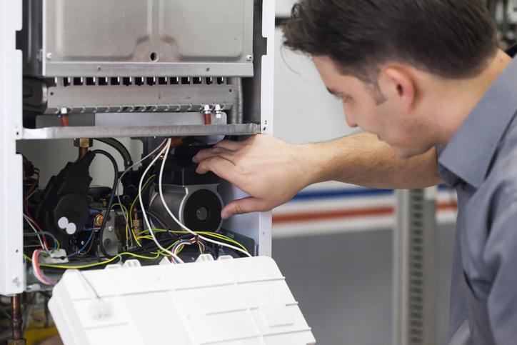 Un technicien fait l'entretien d'une chaudière