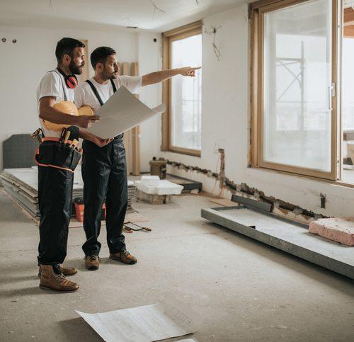 Deux professionnels du bâtiment se consultant sur un chantier