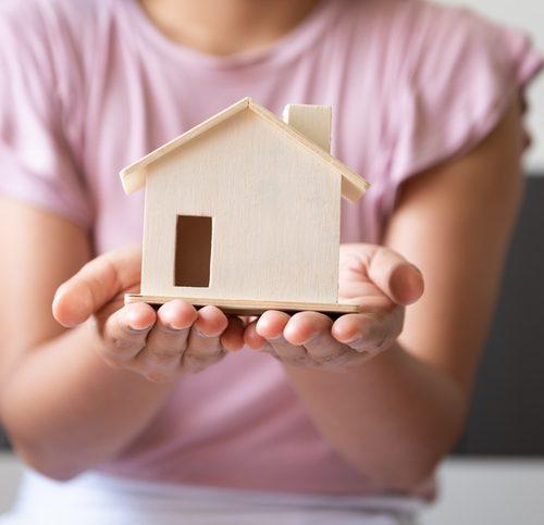mains-qui-portent-maison-miniature