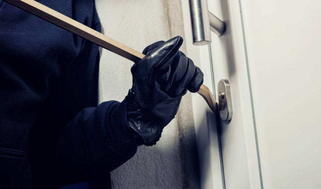 homme forçant une porte d'entrée avec un pied de biche