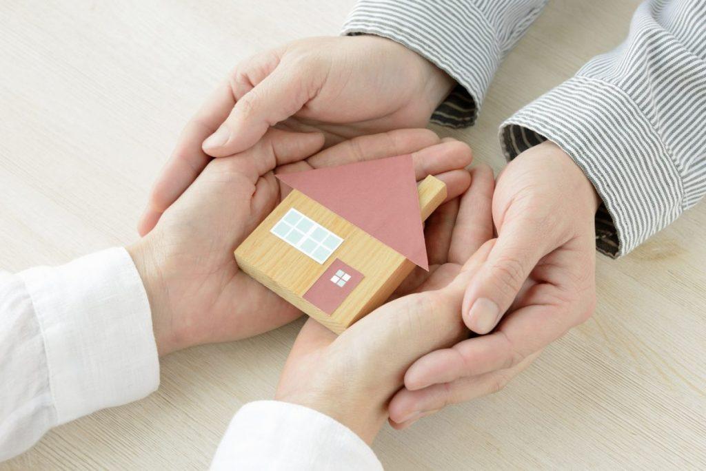 mains qui se touche avec maison en bois miniature