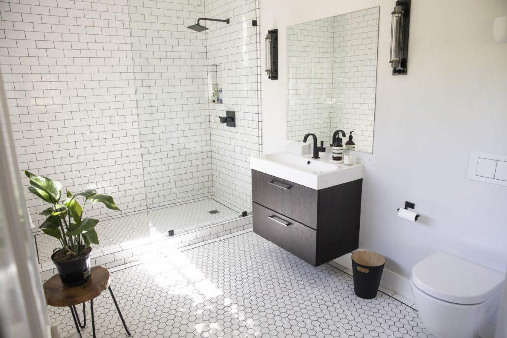 salle de douche avec carrelage blanc partout douche a l'italienne avec paroi vitrée et meuble vasque suspendu noir