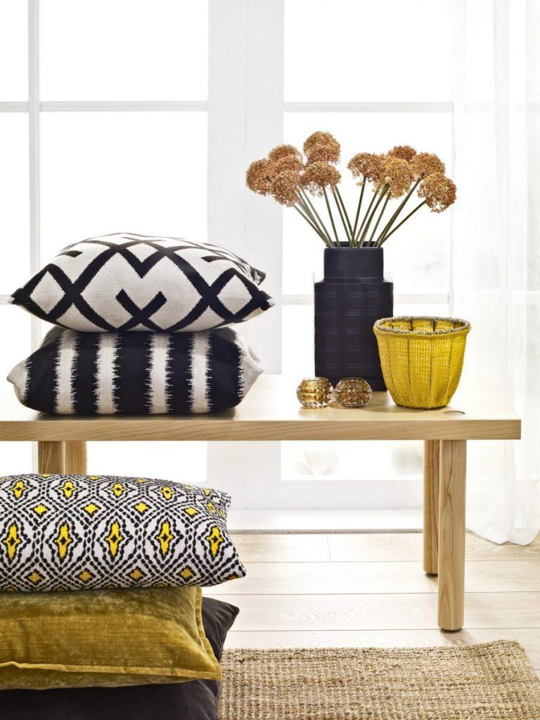 banc en bois avec vase de fleurs séchées et coussin jaune noir et blanc