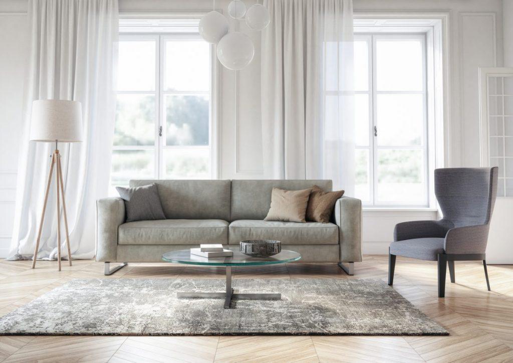 salon parquet clair avec tapis canapé et fauteuil gris dans une pièce avec mur blanc