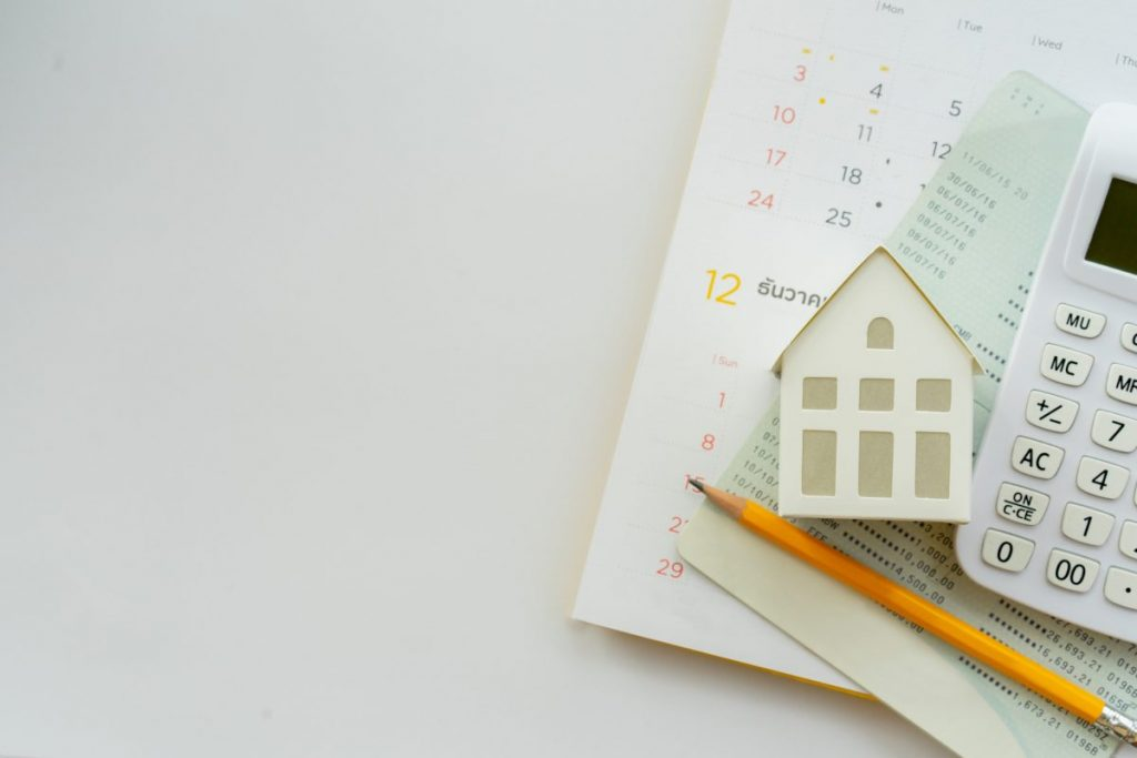 table avec calculette petite maison en papier crayon et pile de papier