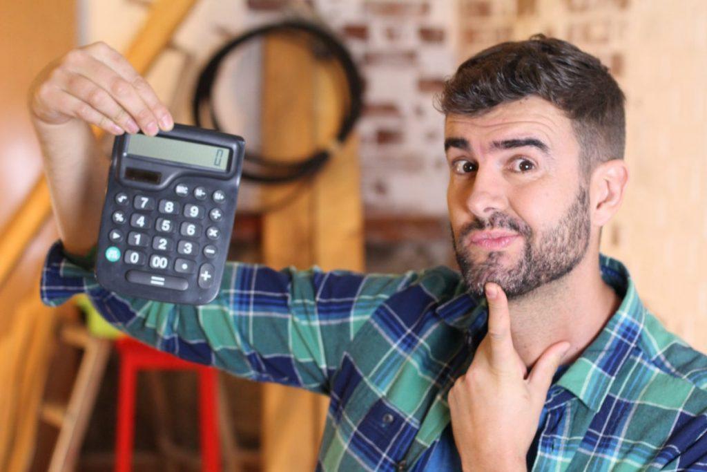 homme tenant une calculatrice dans un atelier