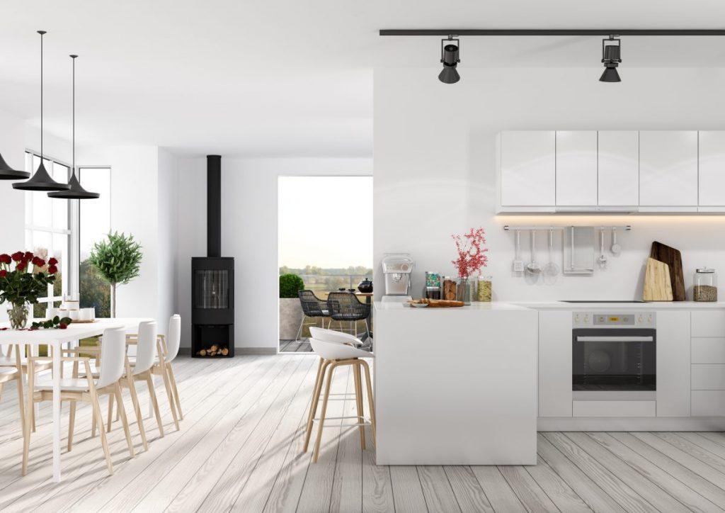 séjour avec cuisine ouverte blanche salle a manger blanche et poêle a bois noir dans appartement en rez-de-chaussée