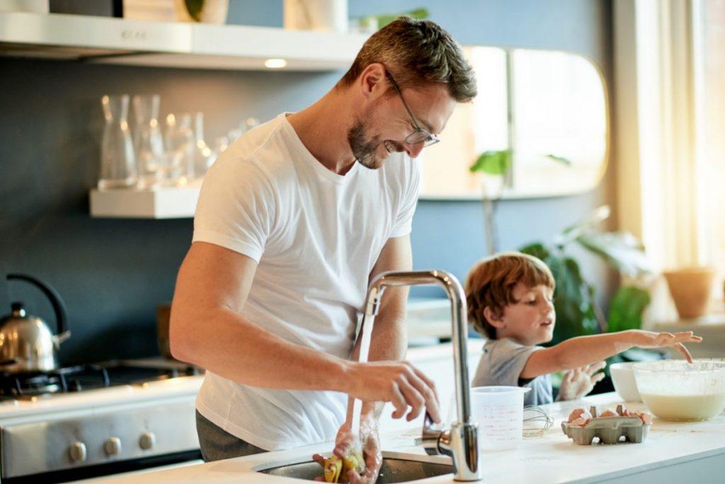 homme-et-son-fils-font-couler-de-l-eau-dans-la-cuisine