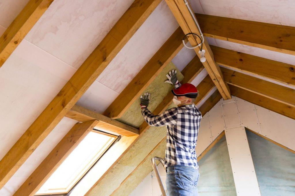 homme installant isolant sous les toits