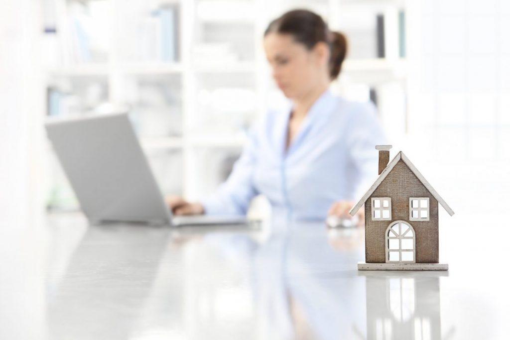 maison en papier sur table blanche avec femme et ordinateur en arrière plan