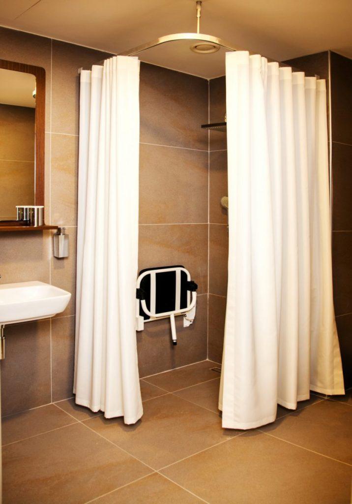 une douche avec rideau et siège pour PMR