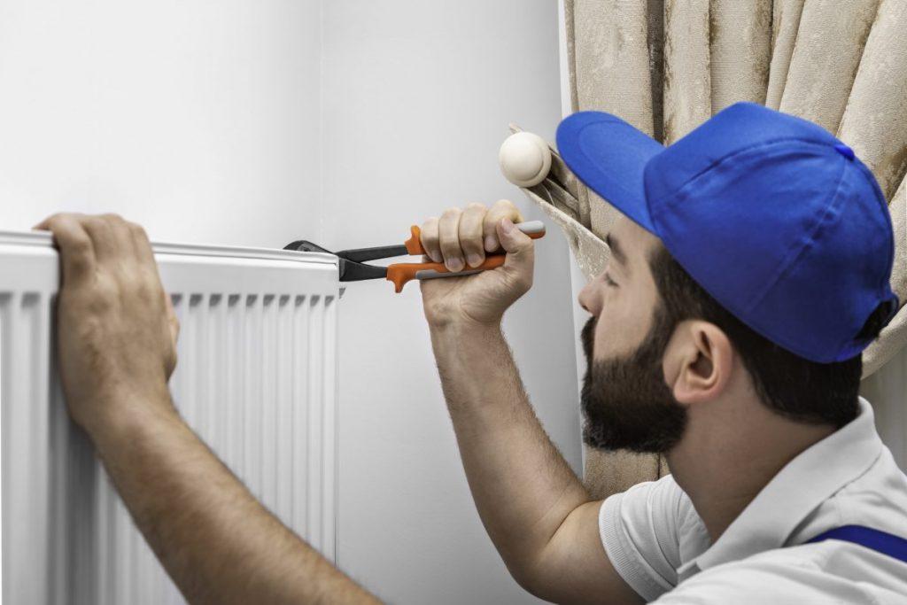 plombier réparant un radiateur blanc