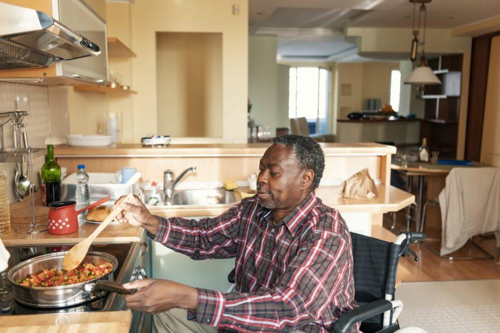 homme handicapé en train de cuisiner dans son logement adapté