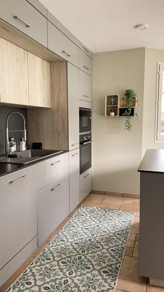 cuisine beige avec élément en bois îlot central et tapis a motif gris