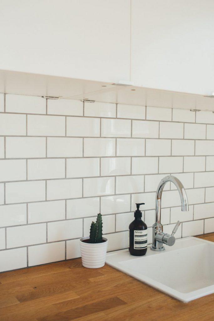 évier de cuisine sur plan de travail bois avec crédence carrelage métro blanc et robinetterie intox