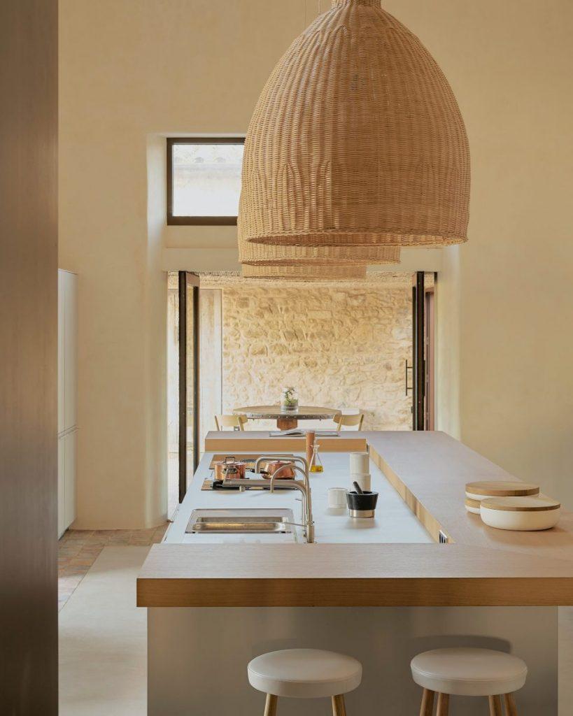 une cuisine moderne a la deco douce avec un ilot central en bosi et des suspensions en rotin