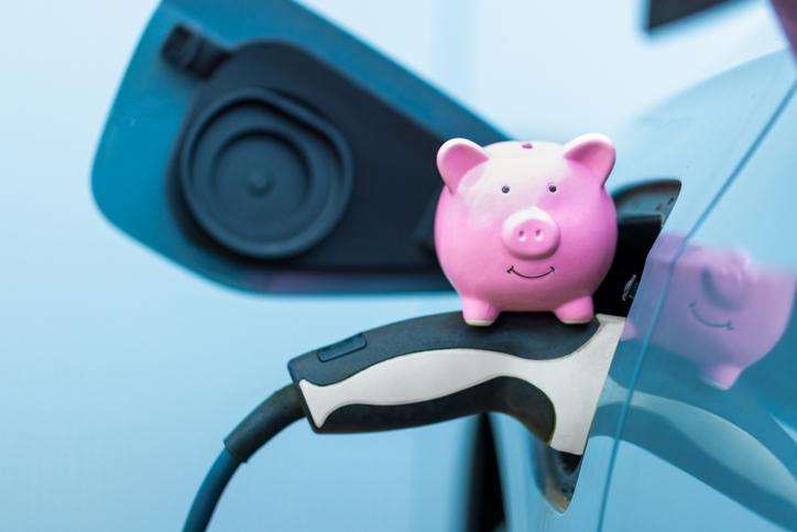 tirelire-cochon-rose-sur-une-voiture-électrique